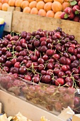 A heap of cherries in a crate at a market