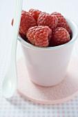 Raspberries in pottery beaker, with spoon