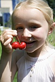 Blond girl holding a pair of cherries