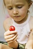 Kleines Mädchen hält eine Kirsche