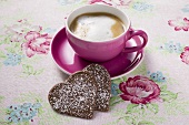 Cup of cappuccino with two chocolate hearts