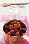 Fresh raspberries in a pan, empty jam jars behind