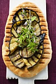 Grilled aubergine slices and herbs on pizza bread
