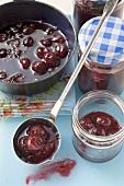 Ladling cherry jam into jars