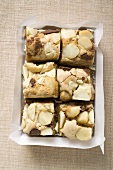 Small pieces of chocolate slice with macadamia nuts in box
