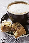 Cappuccino & pieces of chocolate cake with macadamia nuts