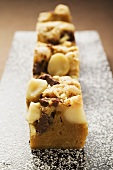 Small pieces of chocolate slice with macadamia nuts on board