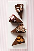 Four pieces of chocolate tart with different decorations