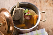 Broth with beef and soup vegetables in pot