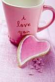 Heart-shaped biscuit in front of mug with the words 'I love you'