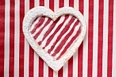 Heart-shaped biscuit with red and white striped icing