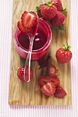 Jar of strawberry jam & fresh strawberries on chopping board