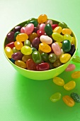 Coloured jelly beans in and beside green bowl