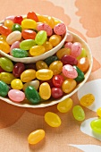 Coloured jelly beans in and beside two bowls