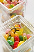 Coloured jelly beans in two storage jars (close-up)