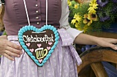 Woman in national dress with Lebkuchen heart at Oktoberfest