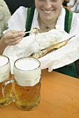 Woman eating Steckerlfisch (skewered fish) at Oktoberfest, beer