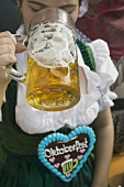 Woman drinking litre of beer at Oktoberfest