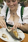 Woman eating Steckerlfisch (skewered fish) at Oktoberfest