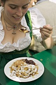 Woman eating scrambled pancake with plum compote at Oktoberfest