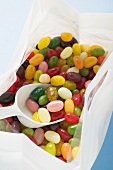 Coloured jelly beans in plastic bag with scoop (detail)