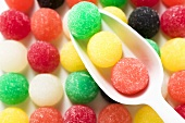 Coloured jelly sweets in rows with scoop (close-up)