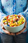 Hands holding a bowl of coloured jelly beans