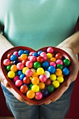 Hands holding a heart-shaped dish of bubble gum balls
