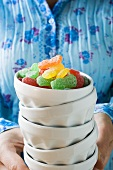 Hands holding pile of bowls with jelly sweets in top bowl