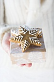 Hands holding gingerbread stars on small box