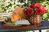 Squashes, pumpkins and flowers on table in the open air