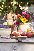 Rustic fruit still life on garden table in front of farmhouse