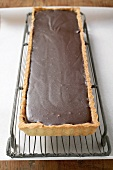 Rectangular chocolate tart on cake rack