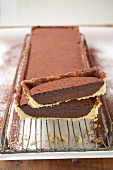 Rectangular chocolate tart with cocoa powder, a piece cut