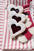 Heart-shaped biscuits with raspberry jam and icing sugar