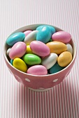 Coloured sugared almonds in pink bowl