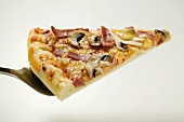 Slice of American-style ham and mushroom pizza