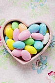 Coloured sugared almonds in pink heart-shaped dish