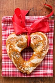 Heart-shaped lye roll with red bow on tea towel