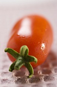 Plum tomato with drops of water (close-up)