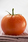 Tomato with drops of water on tea towel