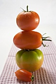 Various types of tomatoes on tea towel (in a pile)