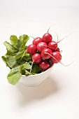 A bunch of radishes in a white bowl