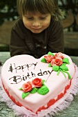Child with pink heart-shaped birthday cake with marzipan roses