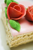 Piece of birthday cake with marzipan roses (close-up)