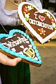 Hands holding Lebkuchen hearts (Oktoberfest, Munich)