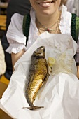 Woman holding Steckerlfisch (fish on stick, Oktoberfest, Munich)