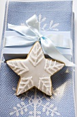 Gingerbread star with white icing in front of gift