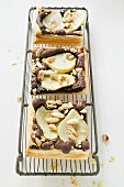 Three pieces of pear & chocolate tart with almonds on rack