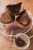 Chocolate buns on cake rack, cocoa powder in sieve
